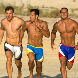 three men running on beach